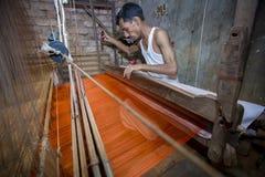 En Jamdani sareearbetare som arbetar på för mycket äldre och långsammare maskiner Arkivfoto