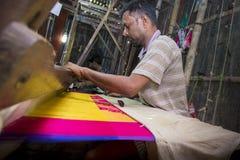 En Jamdani sareearbetare som arbetar en rosa gungarulle Arkivbild