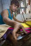 En Jamdani sareearbetare som lägger tillbaka en rosa gungarulle Royaltyfri Bild