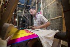 En Jamdani sareearbetare som lägger tillbaka en rosa gungarulle Royaltyfria Bilder