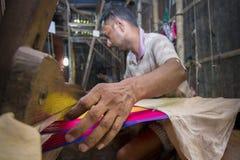 En Jamdani sareearbetare som lägger tillbaka en rosa gungarulle Arkivfoton