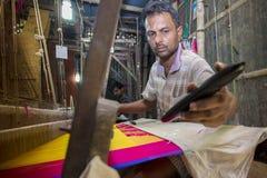 En Jamdani sareearbetare som lägger tillbaka en rosa gungarulle Royaltyfri Fotografi