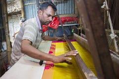 En Jamdani sareearbetare som lägger tillbaka en rosa gungarulle Fotografering för Bildbyråer
