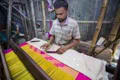 En Jamdani sareearbetare som lägger tillbaka en rosa gungarulle Royaltyfri Foto