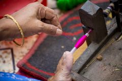 En Jamdani sariarbetare som rullar en rosa gungarulle Arkivbilder
