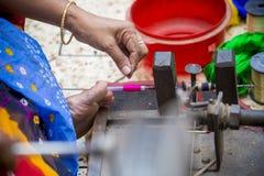 En Jamdani sariarbetare som rullar en rosa gungarulle Fotografering för Bildbyråer