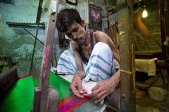 En Jamdani sariarbetare som rullar en rosa gungarulle Arkivbild