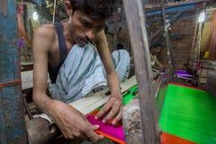 En Jamdani sariarbetare som rullar en rosa gungarulle Royaltyfria Foton