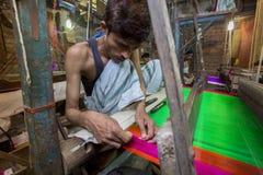 En Jamdani sariarbetare som rullar en rosa gungarulle Arkivfoton