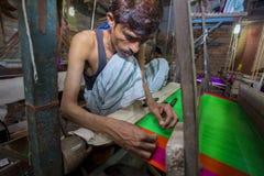 En Jamdani sariarbetare som rullar en rosa gungarulle Royaltyfri Bild