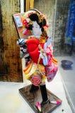 En japansk docka i fönstret Arkivbilder