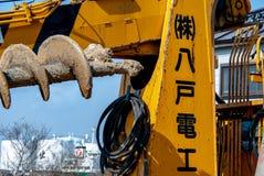 En japansk grävare för installation av elektrisk kabel royaltyfria bilder