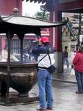 En japansk man ber på den jätte- rökelsekar, innan han skriver in templet arkivbild