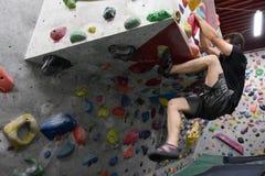 En japansk man som inomhus klättrar en vaggavägg arkivfoto