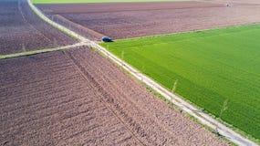 En jeep som korsar en landsväg, av-väg flyg- sikt av en bil som reser en grusväg till och med fälten Royaltyfri Fotografi