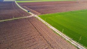 En jeep som korsar en landsväg, av-väg flyg- sikt av en bil som reser en grusväg till och med fälten Royaltyfria Bilder