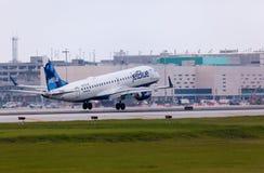 En Jetblue flygbolagEmbraer 190 flygplanslandning royaltyfria foton