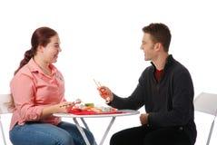 En jongen en meisje die spreken eten Stock Foto's
