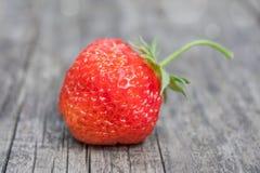 En jordgubbe på en träyttersida Arkivfoto