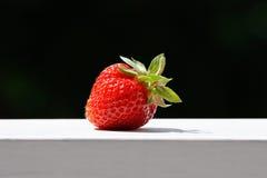 En jordgubbe på en wood räcke fotografering för bildbyråer