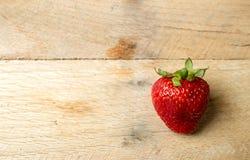En jordgubbe på lantlig wood bakgrund arkivfoton