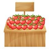 En jordgubbeställning med en tom träskylt Arkivfoto