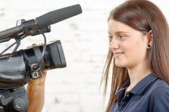 En journalist för ung kvinna ser kameran Arkivbilder