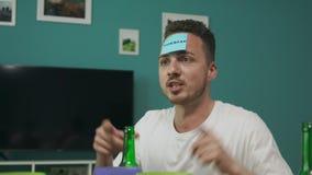 En jugar de los amigos de la sala de estar qui?n son yo juego con los papeles pegajosos en la cabeza almacen de metraje de vídeo