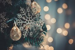 En julgran dekorerade med snöflingor och en girland på bakgrunden av en bokeh och vita bräden Glad jul, idéer för Royaltyfri Bild