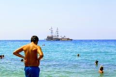 En julio de 2017 - un hombre en pantalones cortos azules que toma el sol en la costa en Cleopatra Beach Alanya, Turquía Fotos de archivo libres de regalías