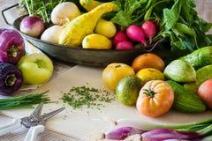 En kökplats med klippta gräslökar och nytt tvättade grönsaker royaltyfri foto