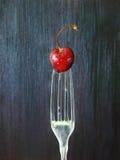 En körsbär på en gaffel Arkivbild