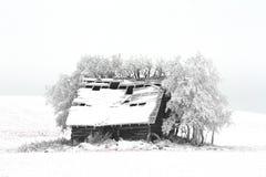 En kabin i ett snöig fält Arkivbild