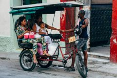 En kabukitaxi tappar av en familj på deras destination i havannacigarren, Kuba fotografering för bildbyråer