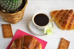En kaffekopp med espresso, giffel, kex, kaktus i korgen, orkidé på en trämålad bakgrund Arkivbild