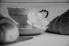 En kaffekopp med varm espresso, giffel, tabell-servetten och orkidén blommar på en träbakgrund som är svartvit Royaltyfri Bild
