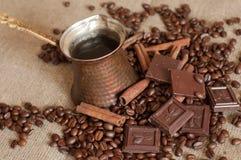 En kaffekruka, grillade kaffebönor, kanelbruna pinnar och stycken av choklad på en säckväv Arkivbild