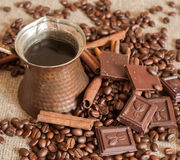 En kaffekruka, grillade kaffebönor, kanelbruna pinnar och stycken av choklad på en säckväv Royaltyfria Foton