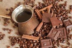 En kaffekruka, grillade kaffebönor, kanelbruna pinnar och stycken av choklad på en säckväv Arkivbilder