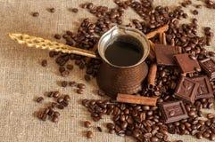 En kaffekruka, grillade kaffebönor, kanelbruna pinnar och stycken av choklad på en säckväv Royaltyfria Bilder