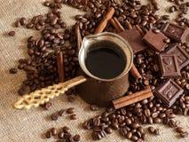 En kaffekruka, grillade kaffebönor, kanelbruna pinnar och stycken av choklad på en säckväv Royaltyfri Foto