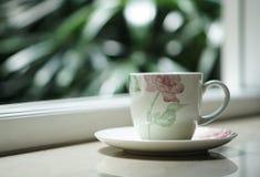 En kaffetekopp vid fönstret med utomhus- sikt Royaltyfri Bild