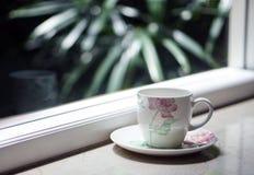 En kaffetekopp vid fönstret med utomhus- sikt Arkivfoto