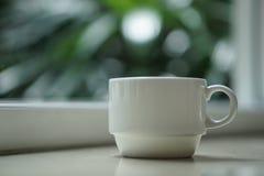 En kaffetekopp vid fönstret med utomhus- sikt Arkivbild