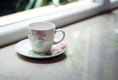 En kaffetekopp vid fönstret med utomhus- sikt Arkivbilder