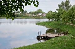 En kaj nära en flod som omges av träd Fotografering för Bildbyråer