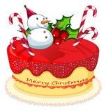 En kaka med en snögubbe, rottingar och en julstjärnaväxt Royaltyfri Bild