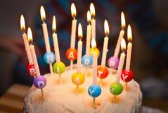 En kaka och det är stearinljus som läser lycklig födelsedag Royaltyfri Bild
