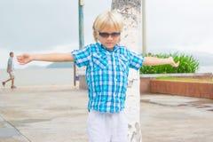 En kall blond pojke i solglasögon som går i en parkera med armar upp royaltyfria foton