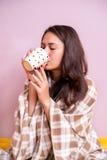 En kall flicka som täckas med en filt som dricker te Fotografering för Bildbyråer